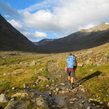 Überwinde das größte Hindernis Europas: Mit Rucksack und Wanderschuhen bei der Alpenüberquerung.