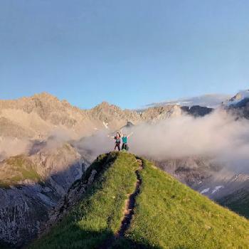 Zwei Wandernde bei unserer Alpenüberquerung auf einem Gipfel