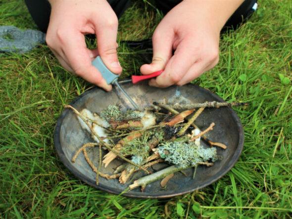 Mit dem Feuerstahl erzeugst Du Funken, die dann das Feuer zum brennen bringen. Beim Into the Wild Wildniscamp kannst Du es ausprobieren.