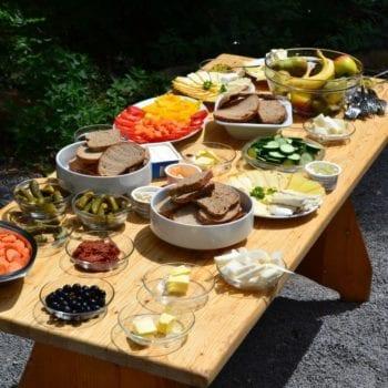 Leckerer Brotzeittisch: Wir verpflegen uns beim Ferienlager für Kinder selbst. Das heißt: Jede*r steht mal als Chefköchin in der Küche, auch Du! :)