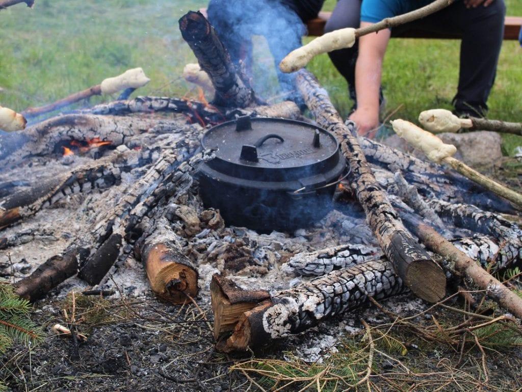 Die letzten Reste der Lagerfeuer-Hitze werden eingefangen, um das Brot zu backen.