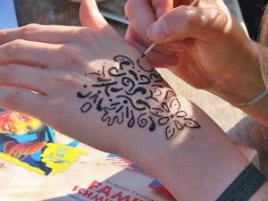 Beim Malen von Henna-Tattoos unter freiem Himmel ohne Vorgaben kreativ sein und Spaß haben