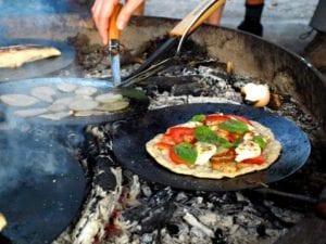Auch leckere Pizza, Omelette oder Crepes können bei Feuer und Flamme am Lagerfeuer gebacken werden